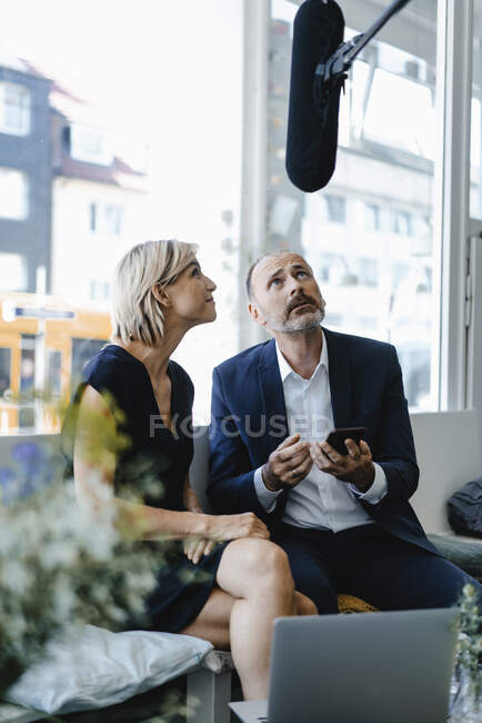 Microphone listening to businesswoman an d man , using smartphone — Stock Photo
