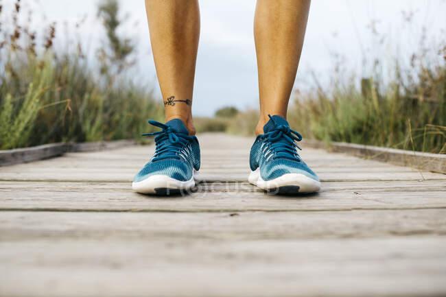 Pés de mulher corredora de pé no calçadão de madeira — Fotografia de Stock