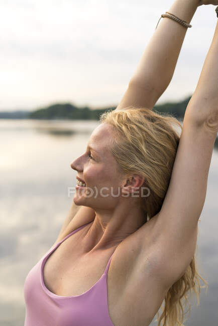 Happy young woman raising her arms at a lake — Stock Photo
