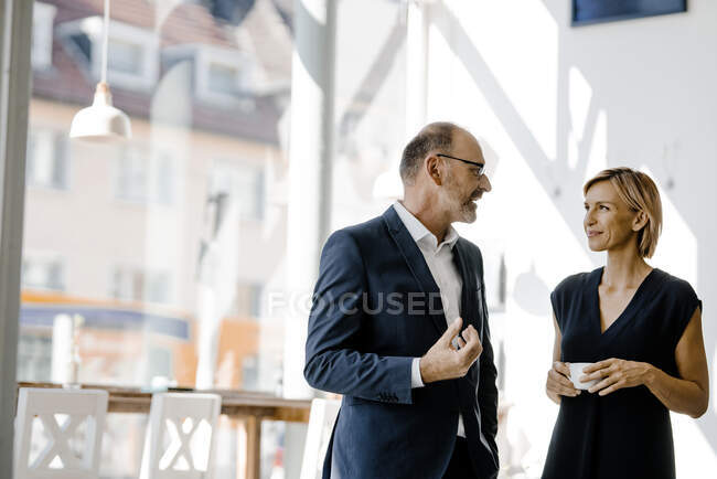 Businessman and woman talking about solutions, drinking coffee — Stock Photo
