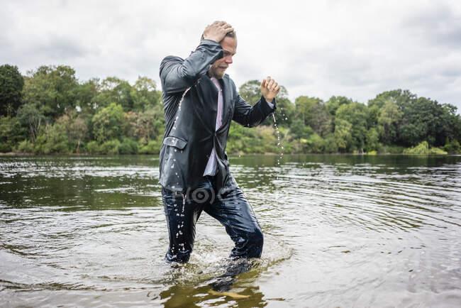Hombre de negocios mojado caminando en un lago - foto de stock
