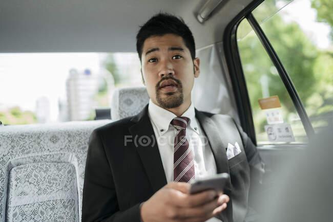 Молодий бізнесмен з мобільним телефоном у таксі розмовляє з водієм. — стокове фото