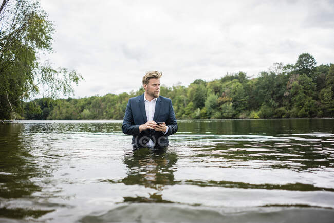 Empresario de pie en un lago con teléfono celular - foto de stock