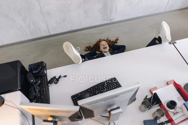 Happy businesswoman lying on the floor in office — Stock Photo