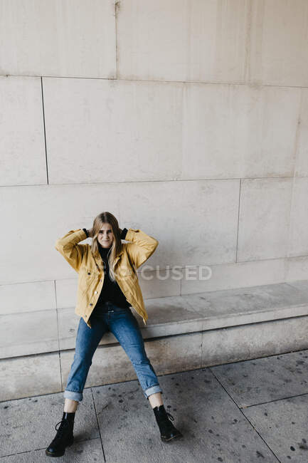 Portrait of young woman wearing jeans and yellow jacket sitting on a wall — Stock Photo