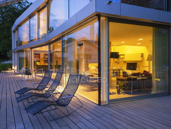 Switzerland, three deck chairs on terrace of lighted modern villa at dusk — Stock Photo