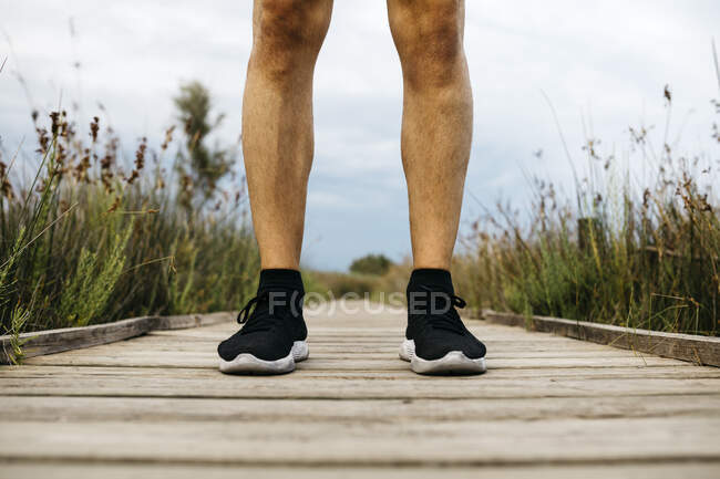 Black running shoes, male jogger standing on a wooden walkway — Stock Photo