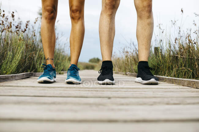 Feet of joggers, standing on a wooden walkway — Stock Photo