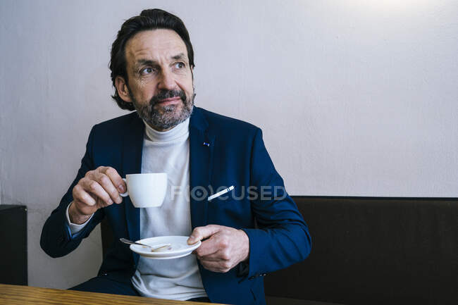 Portrait of mature businessman with cup of coffee in a cafe — Stock Photo