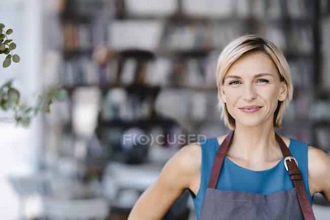 Портрет блондинки, стоящей перед собственной кофейней — стоковое фото