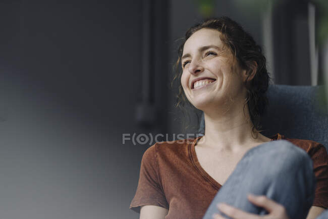 Portrait of laughing young woman sitting on lounge chair at home — Stock Photo