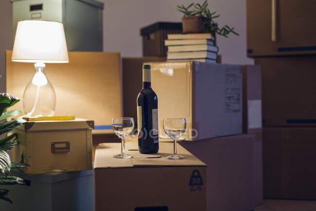 Бутылка вина и бокалы на картонной коробке в пустой комнате в новом доме — стоковое фото