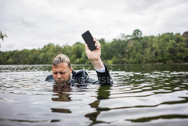Empresario sosteniendo teléfono celular dentro de un lago - foto de stock