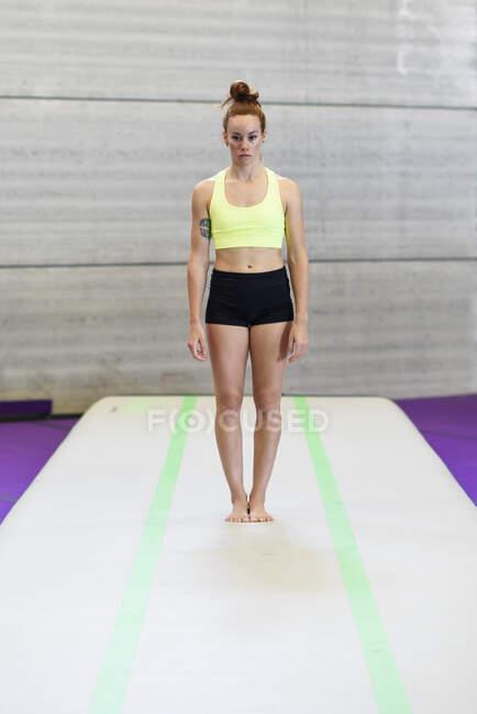 Гимнастка, стоящая на коврике — стоковое фото