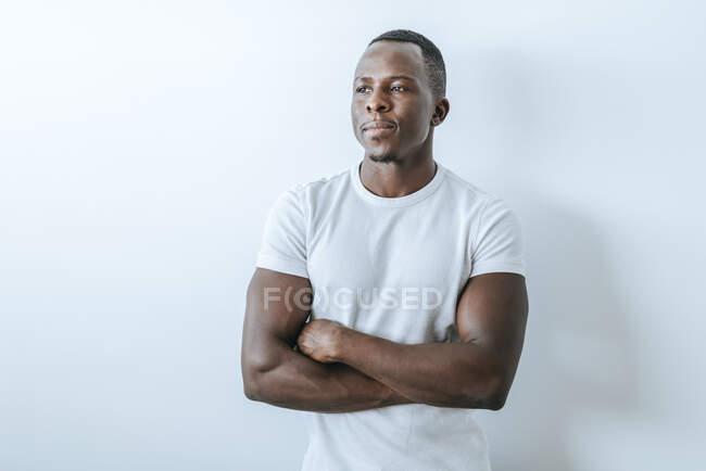 Retrato de un joven confiado frente a una pared blanca - foto de stock