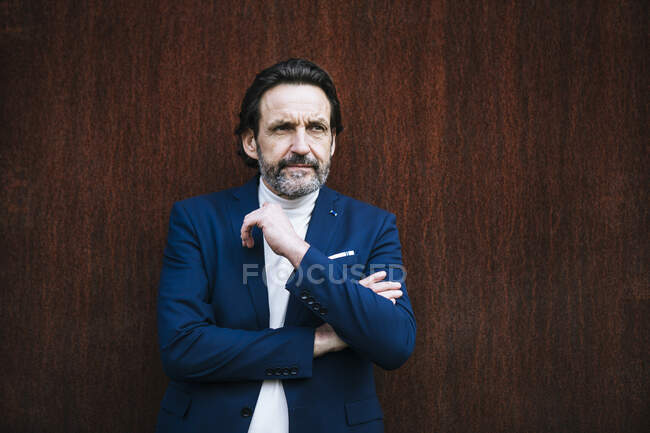 Portrait of mature businessman in front of corten wall — Stock Photo