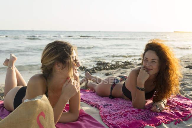 Giovane donna sdraiata su asciugamani in spiaggia — Foto stock