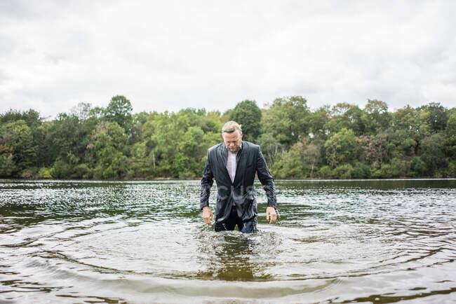 Hombre de negocios mojado en un lago - foto de stock