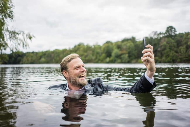 Loco hombre de negocios sosteniendo el teléfono celular dentro de un lago - foto de stock