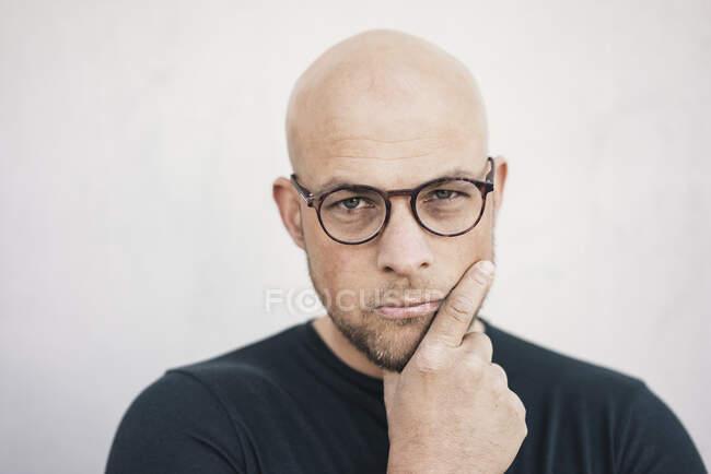 Portrait of starring bald man wearing glasses — Stock Photo