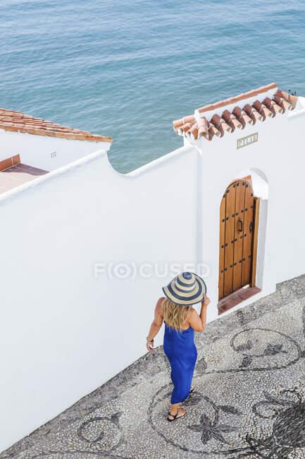 Vista trasera de la mujer con vestido azul y sombrero de paja caminando por el callejón, Nerja, España - foto de stock