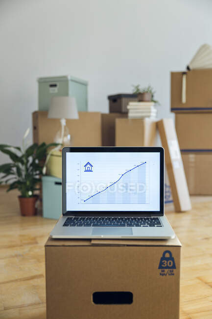 Rising line graph on laptop screen in front of cardboard boxes in an empty room in a new home — Stock Photo