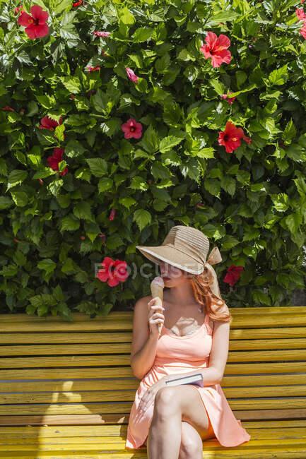 Woman with book sitting on a bench eating icecream, Frigiliana, Malaga, Spain — Stock Photo