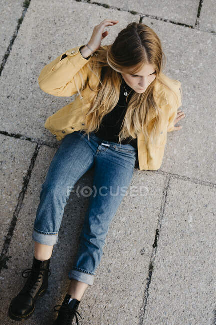 Young woman wearing yellow jacket sitting on the ground — Stock Photo