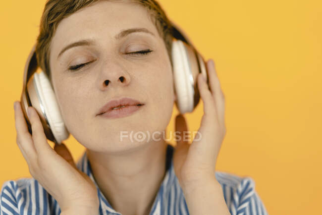 Portrait of woman listening to music with orange background — Stock Photo