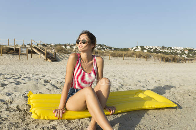 Giovane donna seduta su airbad giallo in spiaggia — Foto stock