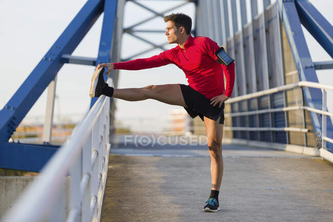 Jogger with smartphone in arm pocket stretching his leg — Stock Photo