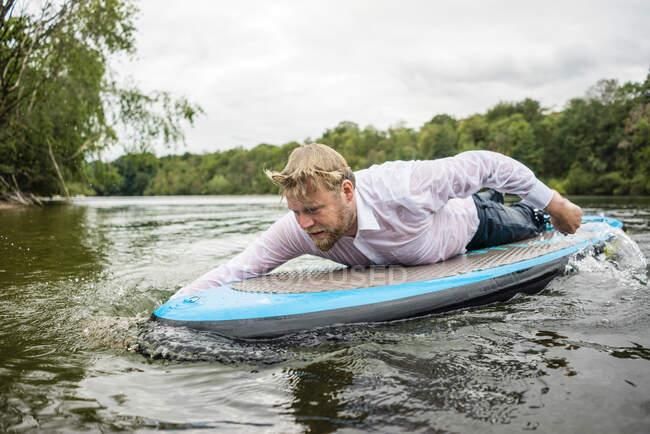 Empresario mojado acostado en una tabla de SUP en un lago - foto de stock