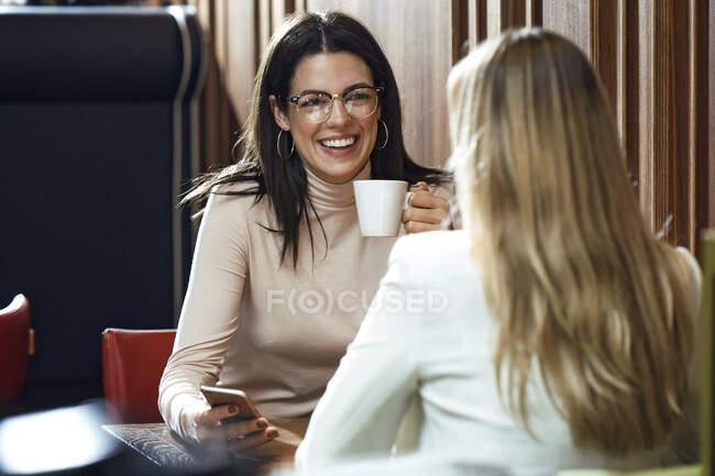 Портрет щасливої жінки з другом у кафе. — стокове фото