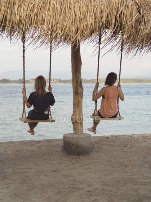 Погляд на двох жінок, які сидять на гойдалках на березі моря (острови Ґілі, Балі). — стокове фото