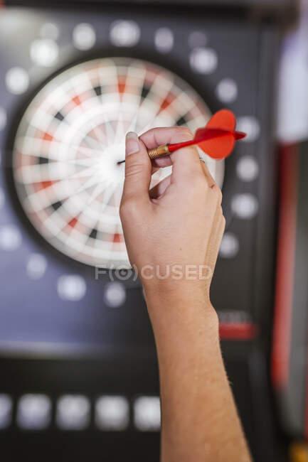 Primer plano de la mano de la mujer sosteniendo dardo delante del tablero de dardos - foto de stock