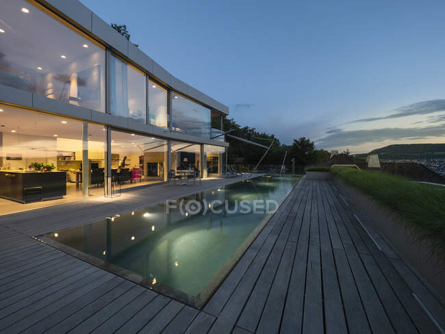 Switzerland, lighted modern villa at dusk with terrace and pool in the foreground — Stock Photo