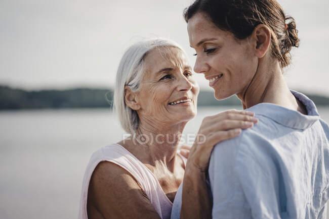Мама з дочкою провели день у морі, обіймаючись на пляжі. — стокове фото