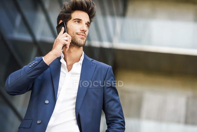 Бізнесмен розмовляє по мобільному телефону біля офісного будинку. — стокове фото