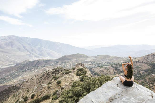 Вид сзади на спортивную молодую женщину, сидящую на скальной смотровой площадке — стоковое фото