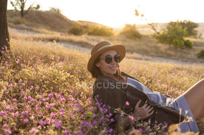 Giovane donna sdraiata sul prato al tramonto — Foto stock