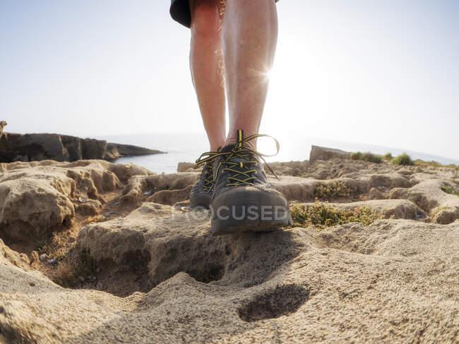 Homem sênior com sapatos de caminhante em pé na rocha, contra o sol — Fotografia de Stock
