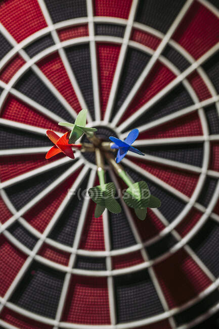 Close-up of darts in bull's eye of electronic dartboard — Stock Photo