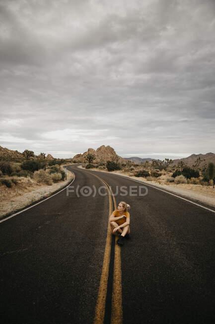 Mujer sentada en la carretera, Joshua Tree National Park, California, EE.UU. - foto de stock