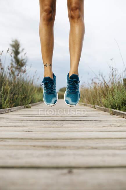 Ноги бегуньи, прыгающие по деревянной дорожке — стоковое фото