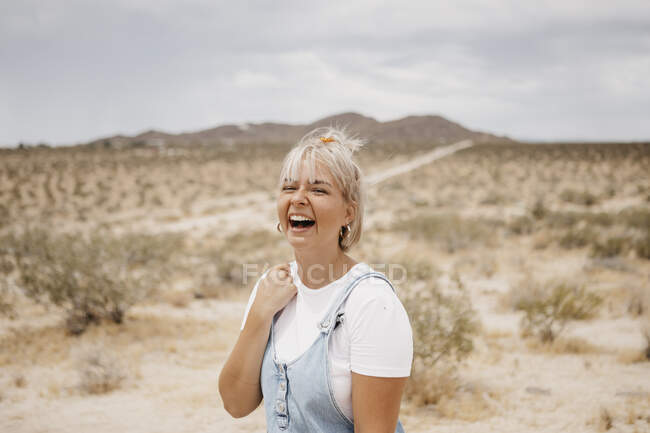 Portrait of laughing young woman in desert landscape, Joshua Tree National Park, California, USA — Stock Photo