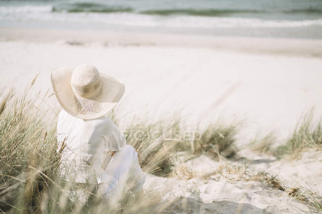 Vista posteriore della donna che indossa un cappello estivo seduta sulla spiaggia guardando il mare, Ruegen, Germania — Foto stock