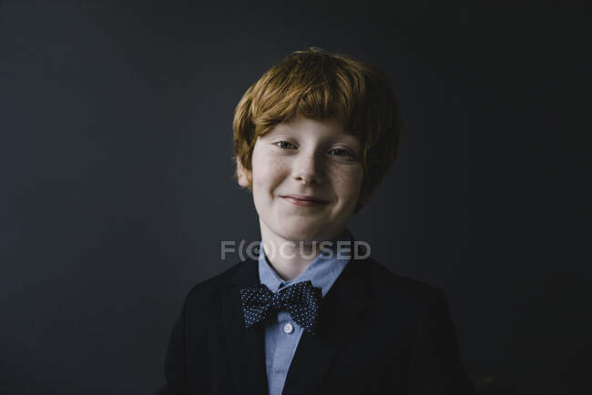 Portrait of smiling redheaded boy wearing bow tie — Stock Photo