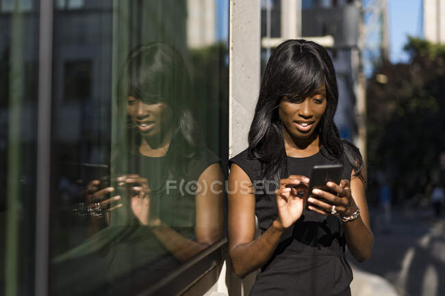Businesswoman using smartphone in the city — Stock Photo