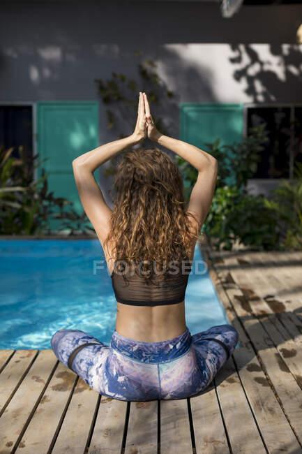 Вид сзади женщины, практикующей йогу у бассейна, Коста-Рика — стоковое фото