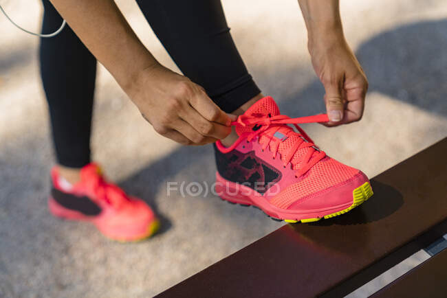 Close-up of sportive young woman tying her shoes — Stock Photo